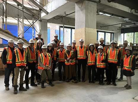 Team picture on construction site wearing high visibility vests and construction helmets