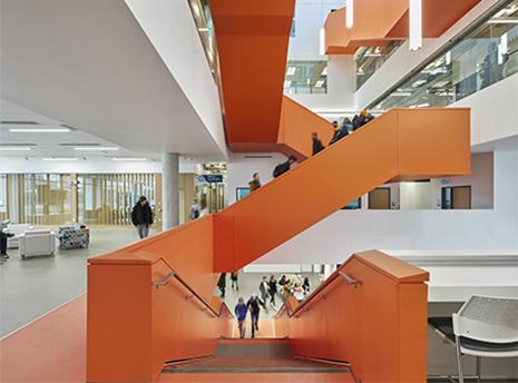 Orange scissor staircase escalating 5 floors through the atrium