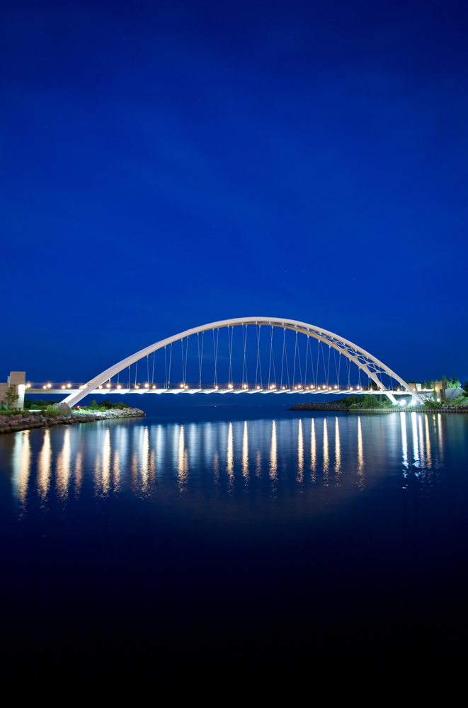The bridge illuminated at night with the lights reflected on the Humber River below