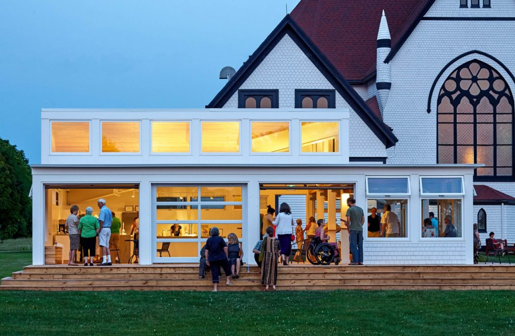 Large gathering in the pavilion which glows in the dusk sky