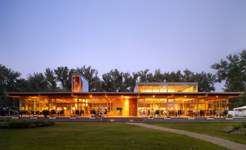 The Island Yacht Club illuminated in the dusk sky with guests sitting on the outdoor patio and indoor dining room